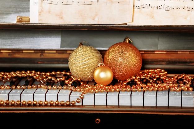 Teclas de piano decoradas com enfeites de natal dourados, close-up