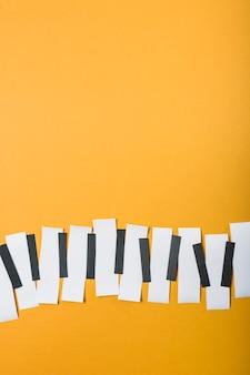 Teclas de piano feitas com papel preto e branco sobre fundo amarelo