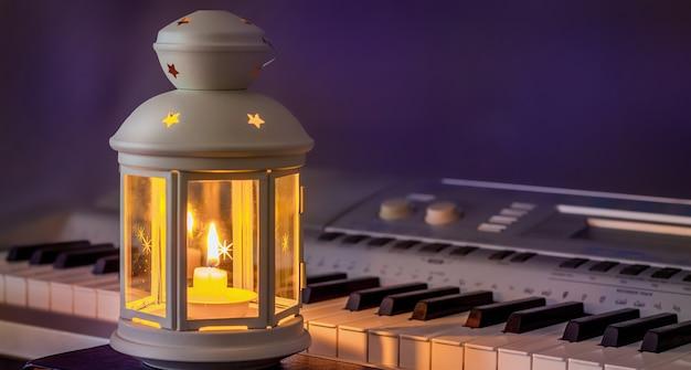 Teclas para piano à luz de uma lanterna com uma vela à noite
