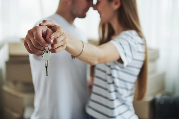 Técnica de foco de imagem. chaves da casa. casal jovem alegre em seu novo apartamento. concepção de movimento. Foto Premium