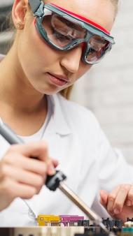 Técnica feminina com ferro de solda e óculos de segurança