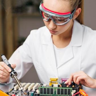Técnica feminina com ferro de solda e placa eletrônica