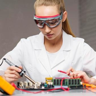 Técnica feminina com ferro de solda e placa-mãe eletrônica
