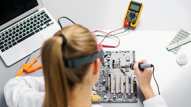 Técnica feminina de alto ângulo com ferro de solda e placa-mãe de eletrônicos