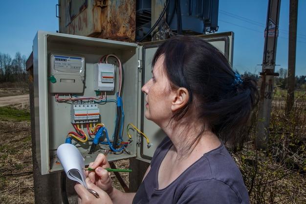 Técnica mulher lendo medidor de eletricidade para verificar o consumo.