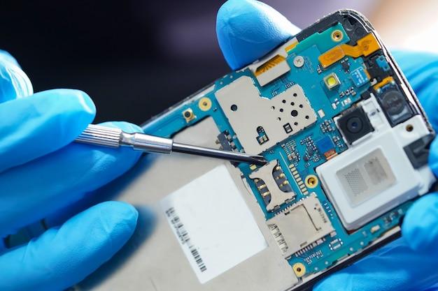 Técnico asiático que repara a placa principal do micro circuito do smartphone.