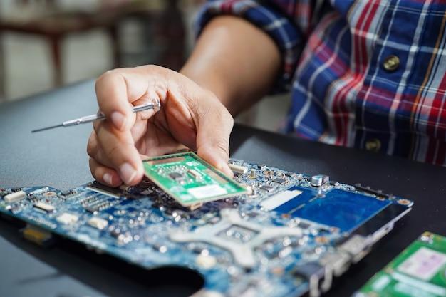 Técnico asiático que repara o computador da placa principal do micro circuito.