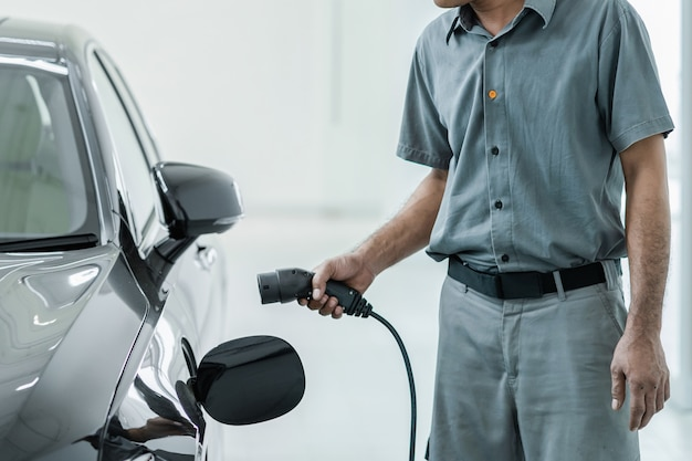 Técnico asiático sênior está cobrando o carro elétrico ou ev no centro de serviço para manutenção