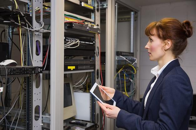 Técnico bonito usando o tablet pc enquanto olha para o servidor no grande centro de dados