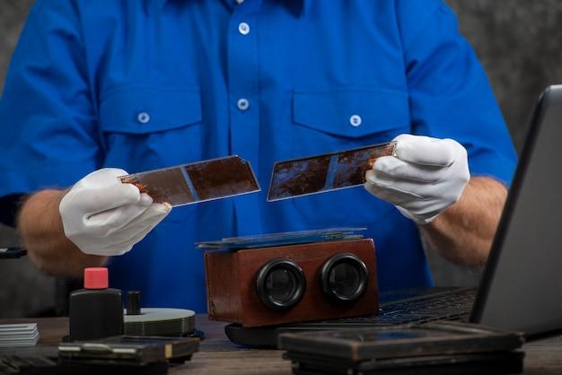 Técnico com luvas brancas, digitalização de fotografia antiga na placa de vidro