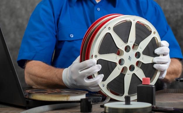Técnico com luvas brancas digitalizando filme antigo 16mm