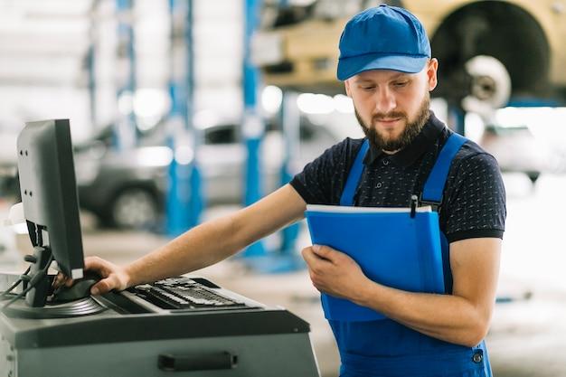 Técnico com pasta e computador na garagem