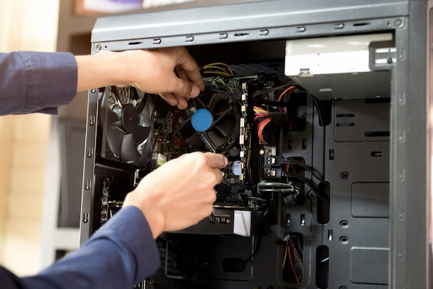 Técnico com uma chave de fenda para consertar computadores, conceitos de hardware de computador.