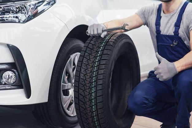 Técnico com uma roupa azul, segurando uma chave inglesa e um pneu enquanto aparece o polegar