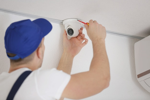 Técnico consertando câmera de vigilância de vídeo