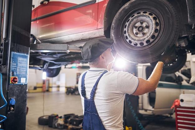 Técnico consertando carro em oficina mecânica