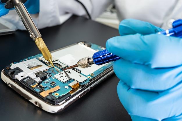 Técnico consertando dentro do telefone celular com ferro de solda