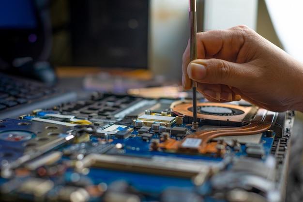 Técnico consertando notebook quebrado com chave de fenda