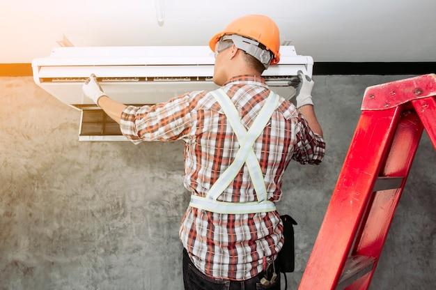 Técnico de ar no conjunto padrão de segurança verificando a qualidade do ar condicionado recém-instalado.
