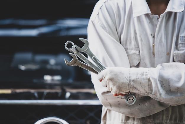 Técnico de automóveis, vestindo um uniforme branco, de pé e segurando uma chave inglesa, que é uma ferramenta essencial para um mecânico