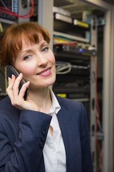 Técnico de computador bonito falando no telefone ao lado do servidor aberto