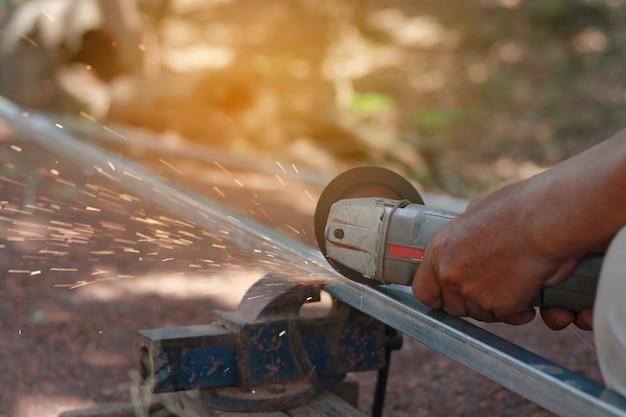 Técnico de corte de aço com ferramenta no local de trabalho.