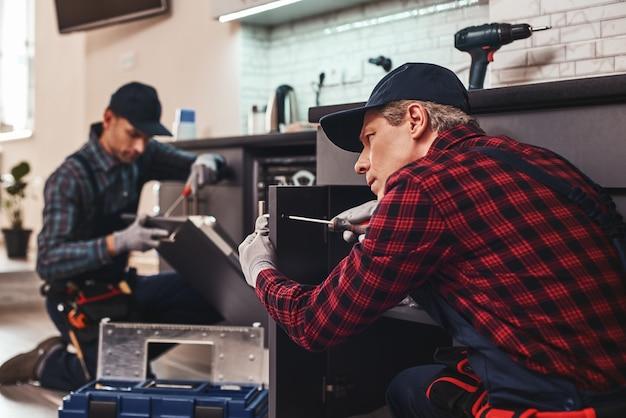 Técnico de dois homens de reparo rápido e de qualidade sentado perto da máquina de lavar louça