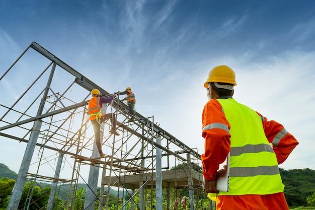 Técnico de engenheiro, assistindo a equipe de trabalhadores na plataforma de aço alta,