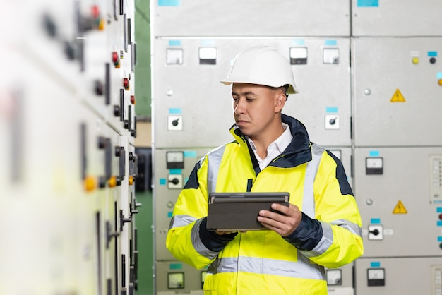 Técnico de engenheiro elétrico asiático segurando tablet monitorando sistema elétrico na sala de controle