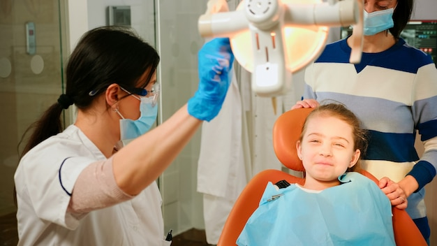 Técnico de estomatologista mulher acendendo a lâmpada para examinar o pequeno paciente sentado na cadeira de estomatologia. médico falando com a garota verificando a saúde dos dentes enquanto a enfermeira prepara ferramentas para o exame