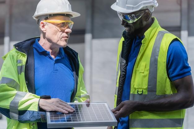 Técnico de fábrica mostrando e verificando célula solar para seu colega de trabalho