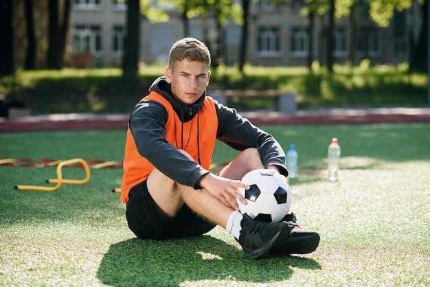 Técnico de futebol profissional com colete laranja e apito no pescoço.