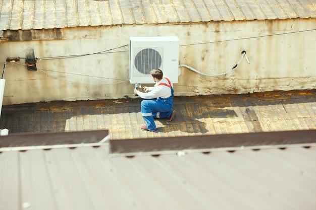 Técnico de hvac trabalhando em uma peça de capacitor para unidade de condensação. trabalhador ou reparador de uniforme reparando e ajustando o sistema de condicionamento, diagnosticando e procurando por problemas técnicos.