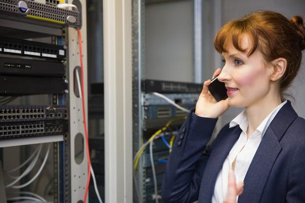 Técnico de informática bonita falando no telefone ao lado do servidor aberto