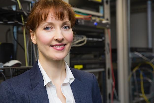 Técnico de informática bonita sorrindo para a câmera ao lado do servidor aberto