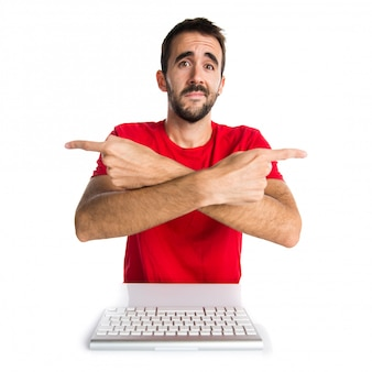 Técnico de informática trabalhando com o teclado apontando para as laterais tendo dúvidas