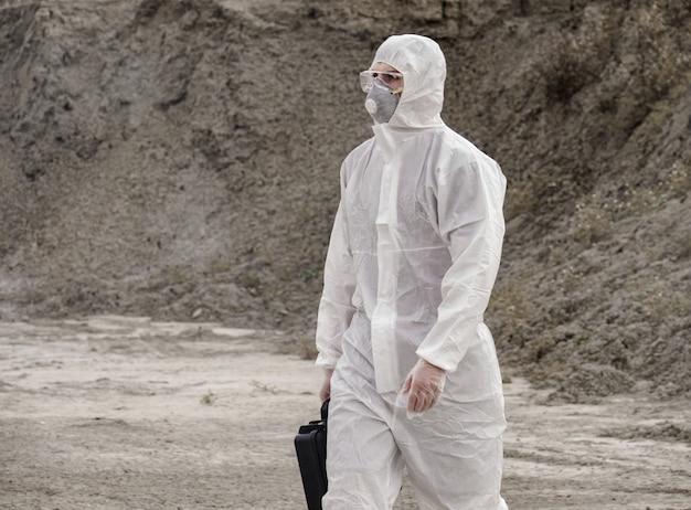 Técnico de laboratório com máscara e roupa de proteção contra produtos químicos, caminha em solo seco com uma caixa de ferramentas em meio à fumaça tóxica.