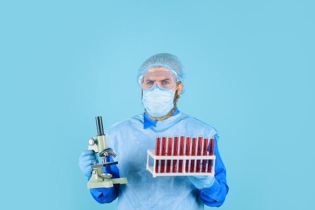 Técnico de laboratório com tubos de teste de sangue e médico microscópico analisando amostra de sangue na clínica