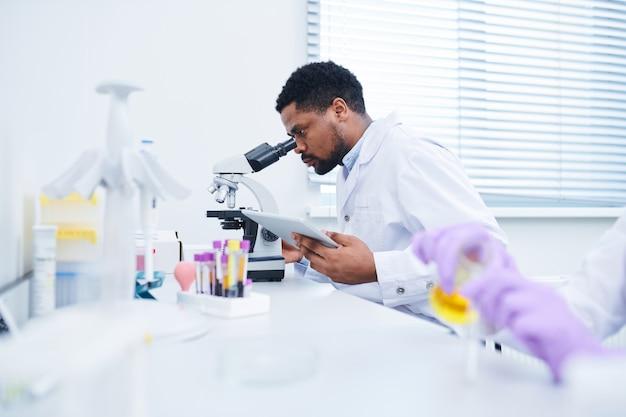Técnico de laboratório concentrado usando microscópio