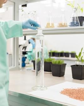 Técnico de laboratório derrama o líquido em frasco alto no fundo do laboratório.