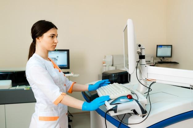Técnico de laboratório profissional está segurando um frasco perto da máquina médica automatizada.