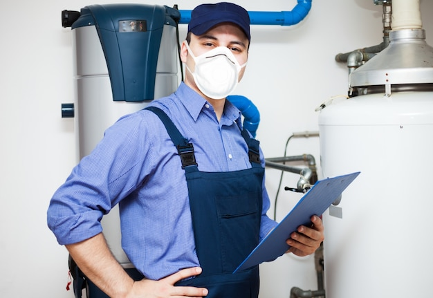 Técnico de manutenção de um aquecedor de água quente durante uma pandemia de coronavírus