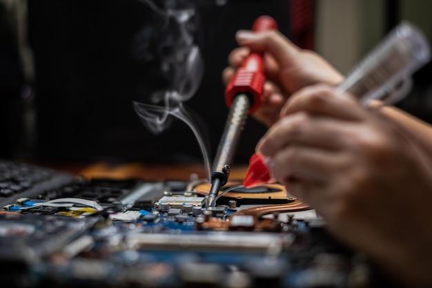 Técnico de mão em close consertando notebook quebrado com ferro de solda elétrico