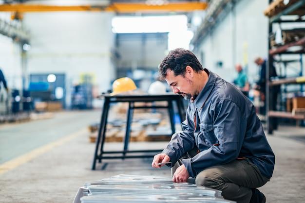 Técnico de medição de peças na fábrica.