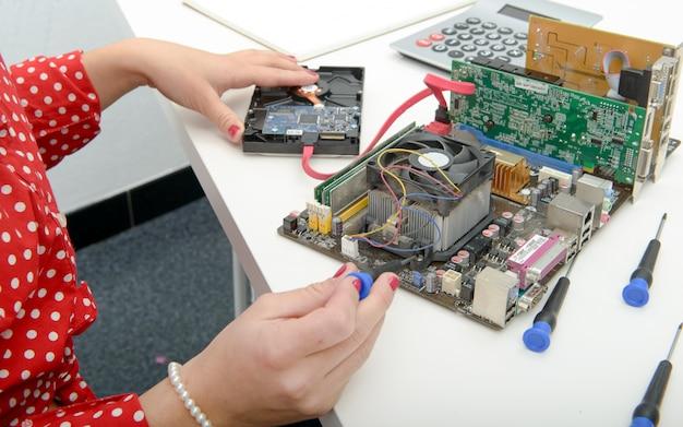 Técnico de mulher repara um computador