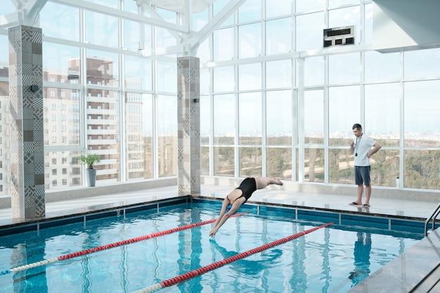 Técnico de natação observando nadador pulando na água, mulher treinando com instrutor em piscina moderna