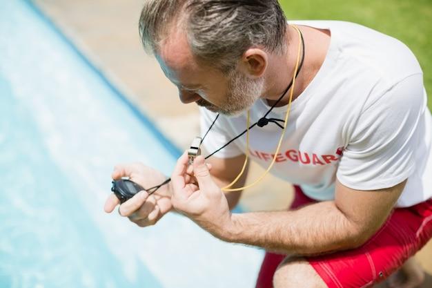Técnico de natação olhando para o cronômetro perto da piscina