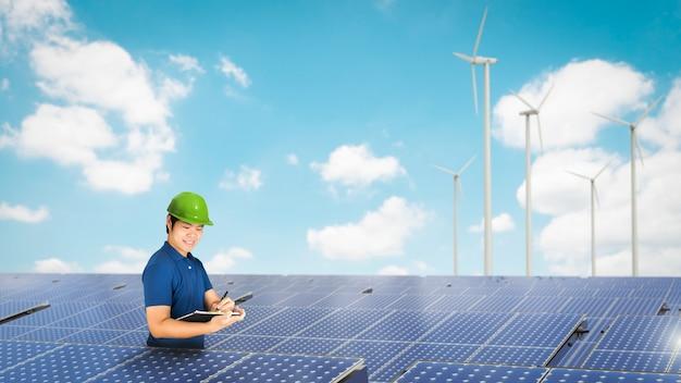 Técnico de painel solar com painel solar e turbinas eólicas