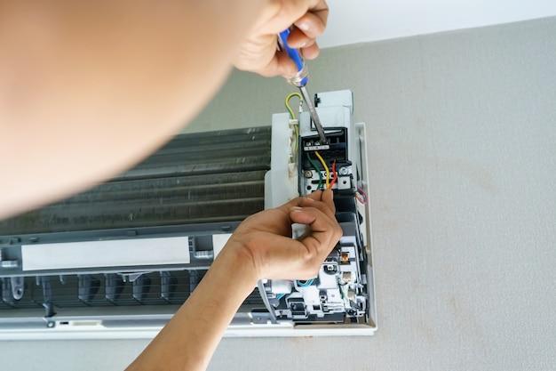 Técnico de reparação de ar condicionado com chave de fenda, instale fios elétricos do ar condicionado