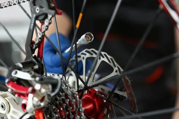 Técnico de reparação de bicicleta de velocidade na oficina close-up